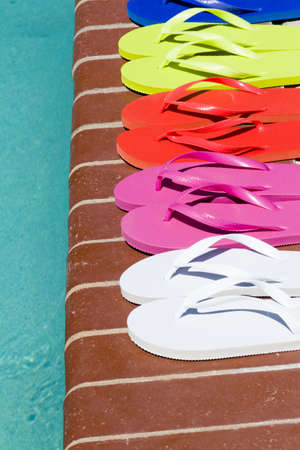 torque: Colorful flip flops by a swimming pool.