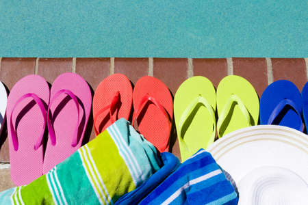 sand lime bricks: Colorful flip flops by a swimming pool.