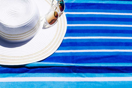 torque: Summer hat with sunglasses on a beach towel.