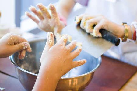 niños cocinando: Mezclar la masa para las galletas en un recipiente grande de metal.