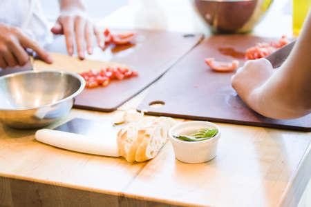 Kinds in cooking class making bruschetta.