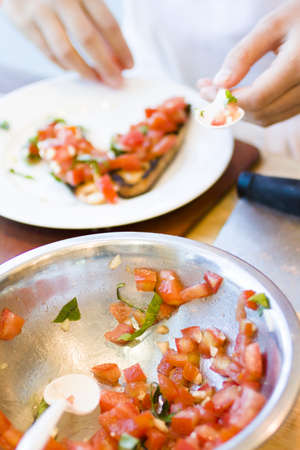 Kinds in cooking class making bruschetta. photo