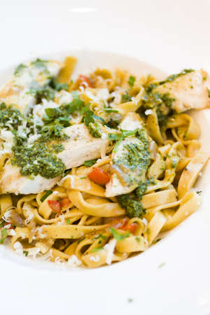 vegetare: Fresh fettucini with chicken, red peppers, and basil pesto.