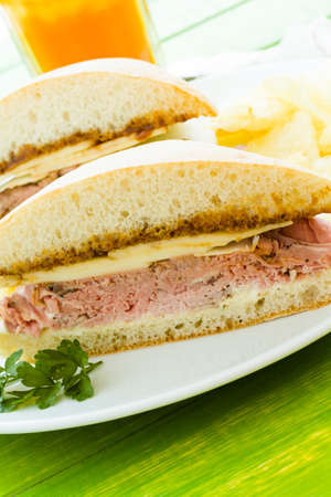 Gourmet roast beef sandwich with chips on the side. photo