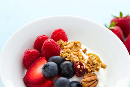 parfait: Parfait with fresh fruits and granola in white bowl.