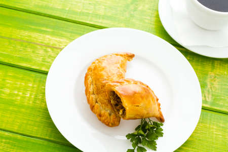 Empanada stuffed with bread on a white plate.