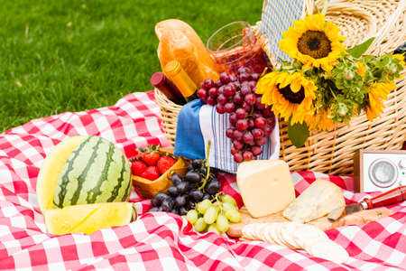 Summer picnic with a basket of food in the park. photo
