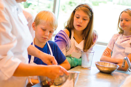 child food: Kids learning how to cook in a cooking class.