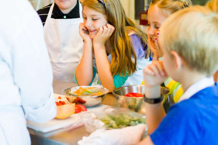 teaching children: Kids learning how to cook in a cooking class.