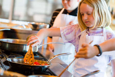 Kids learning how to cook in a cooking class. photo