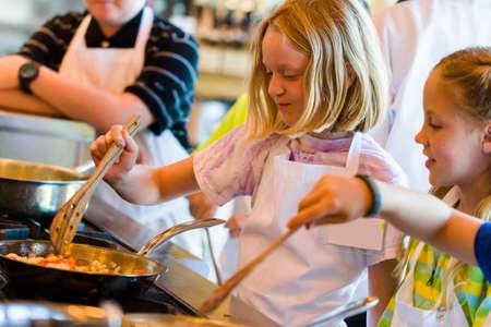 요리 교실에서 요리하는 방법을 배우는 아이.
