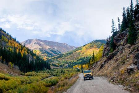Yellow Jeep on Cinnamon Pass in autumn, Colorado.
