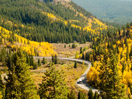 s curve: A rural mountain road with a winding S curve. Autumn landscape in Colorado.