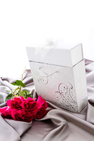 Gift box of assorted gourmet chocolate truffles on silver silk.