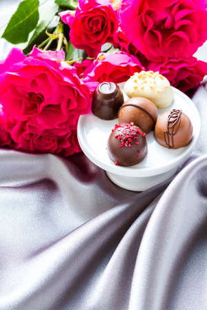 Gourmet chocolate with pink garden roses on silver silk.