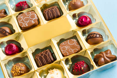fancy sweet box: Gourmet chocolates in golden box on blue  back ground. Stock Photo