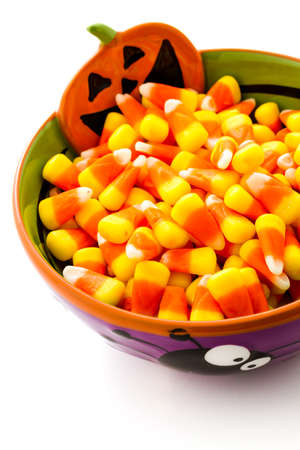 candy corn: Candy corn cadnies in Halloween bowl on a white background. Stock Photo