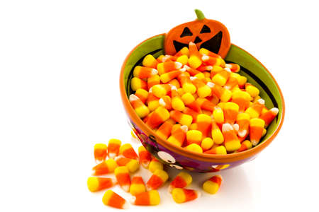 Candy corn cadnies in Halloween bowl on a white background. Stock Photo