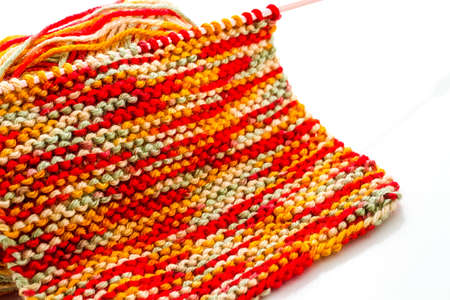Knitting with multi colored yarn with orange, red, and yellow tones. Фото со стока