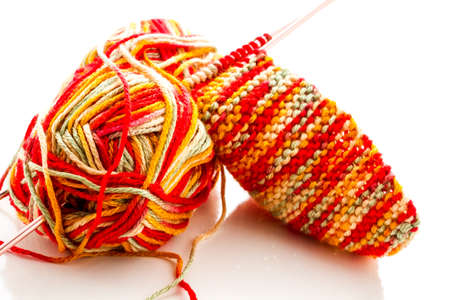 Knitting with multi colored yarn with orange, red, and yellow tones. Imagens