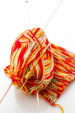 Knitting with multi colored yarn with orange, red, and yellow tones. Stok Fotoğraf