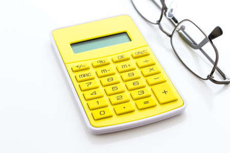 Simple yellow calculator with reading glasses on a white background. Stock Photo