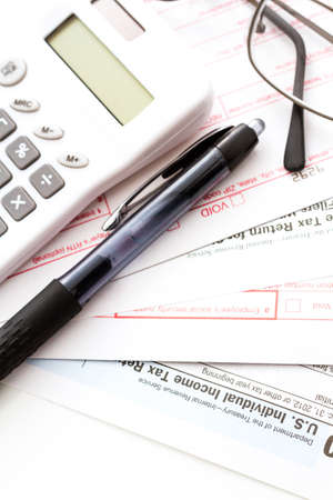 Calculating numbers for income tax return with pen and calculato photo