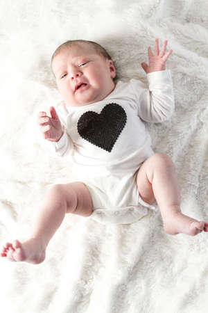Newborn baby girl playing on a white blanket. photo