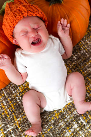 Newborn baby girl in orange pumpkin hat. photo