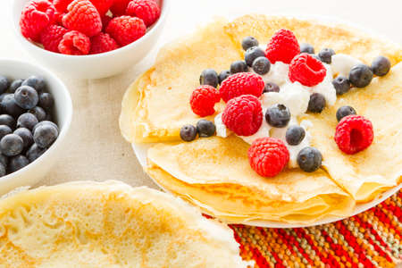Homemade crepes with fresh raspberries and blueberries. Imagens