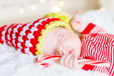 Newborn Christmas baby girl in elf hat on a white blanket. Stock Photo 0001f193195a