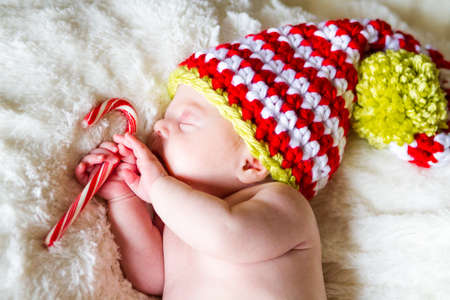 Newborn Christmas baby girl in elf hat on a white blanket. photo