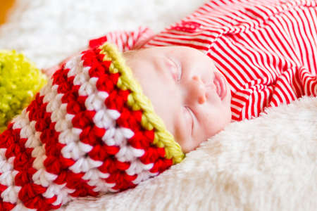 Newborn Christmas baby girl in elf hat on a white blanket. photo