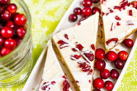 甘いクリーム チーズのアイシングと越えられる白いチョコレートおよび乾燥されたクランベリーのチャンクで作られたクランベリー至福のバー。