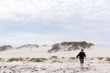 Teenager playing in coastal dunes. photo