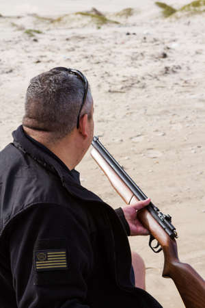 pellet gun: Man loading pellet gun for practice shooting.