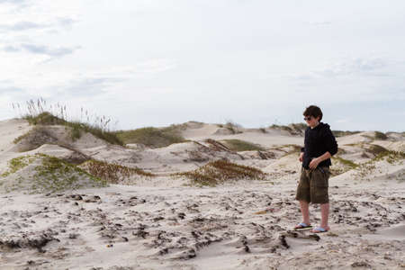 south padre island: Teenager playing in coastal dunes.