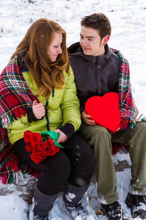 Young couple at the picnic on the Valentines Day in a snowy park. photo