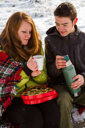 Young couple at the picnic on the Valentines Day in a snowy park.