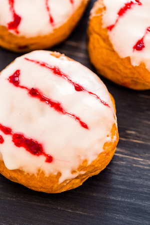 Fresh raspberry jelly filled donuts with white glazing on top. Stock Photo - 25843987