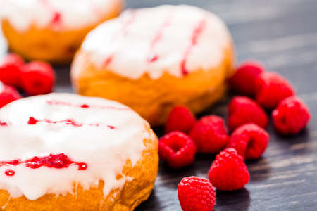 Fresh raspberry jelly filled donuts with white glazing on top. Stock Photo - 25843989
