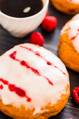 raspberry jelly: Fresh raspberry jelly filled donuts with white glazing on top.