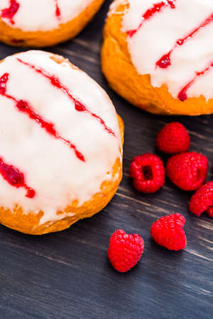 Fresh raspberry jelly filled donuts with white glazing on top. Stock Photo - 25844284