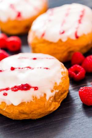Fresh raspberry jelly filled donuts with white glazing on top. Stock Photo - 25844294