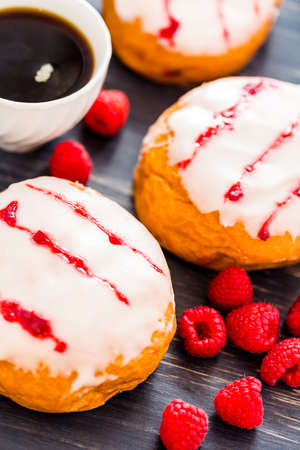 glazing: Fresh raspberry jelly filled donuts with white glazing on top.