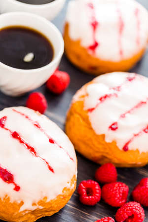Fresh raspberry jelly filled donuts with white glazing on top. Stock Photo - 25844297