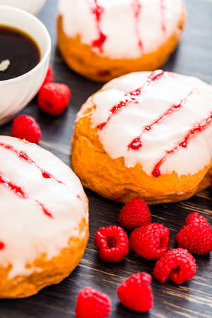 Fresh raspberry jelly filled donuts with white glazing on top. Stock Photo - 25844298