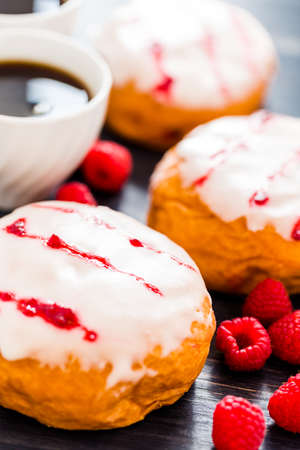 Fresh raspberry jelly filled donuts with white glazing on top. Stock Photo - 25844299