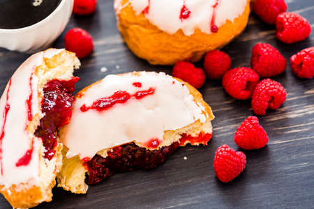 Fresh raspberry jelly filled donuts with white glazing on top. Stock Photo - 25844321