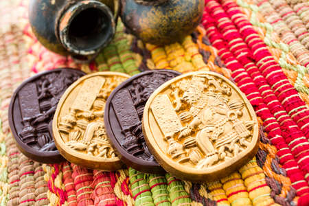Gourmet Maya glyphs in dark chocolate covered with gold dusting. Фото со стока